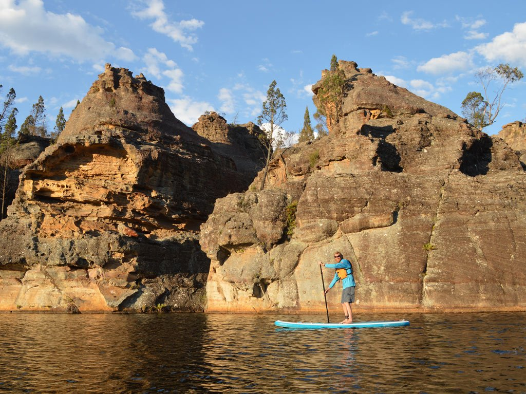 Stand up paddleboarder and pagoda rock formations at Dunns Swamp