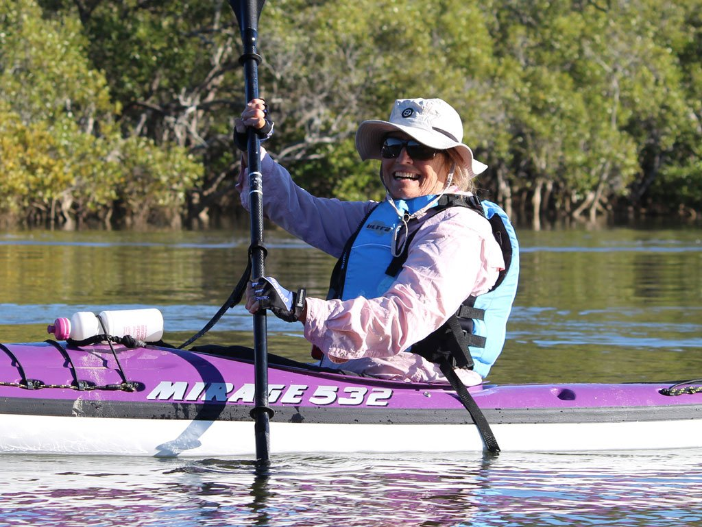 A kayaker wearing sun protection clothing at Cudgera Creek in Hastings Point