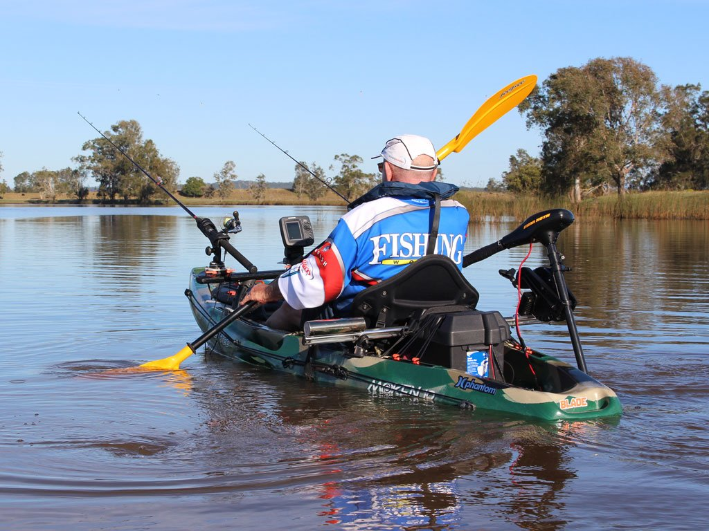 A fisherman paddling a sit on top kayak with fishing gear installed
