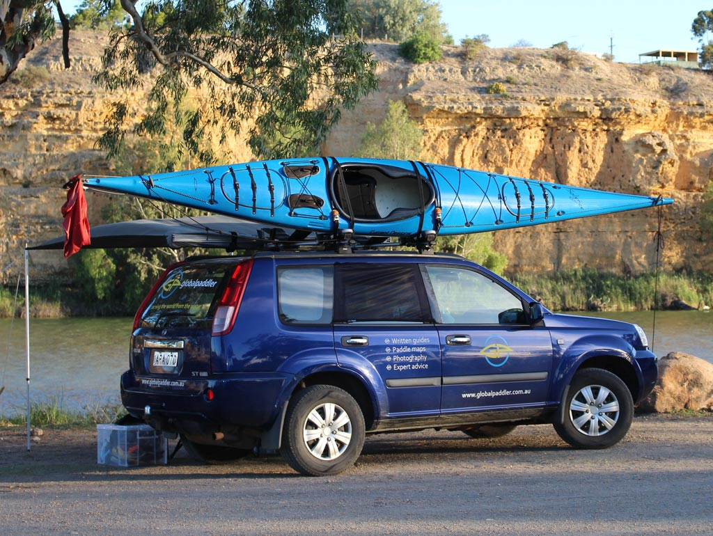 Car with kayak on top beside Murray River in South Australia