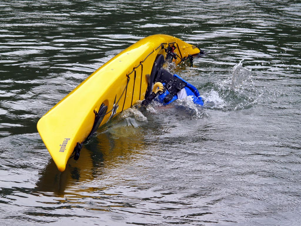 A yellow kayak capsizing with the paddler inside
