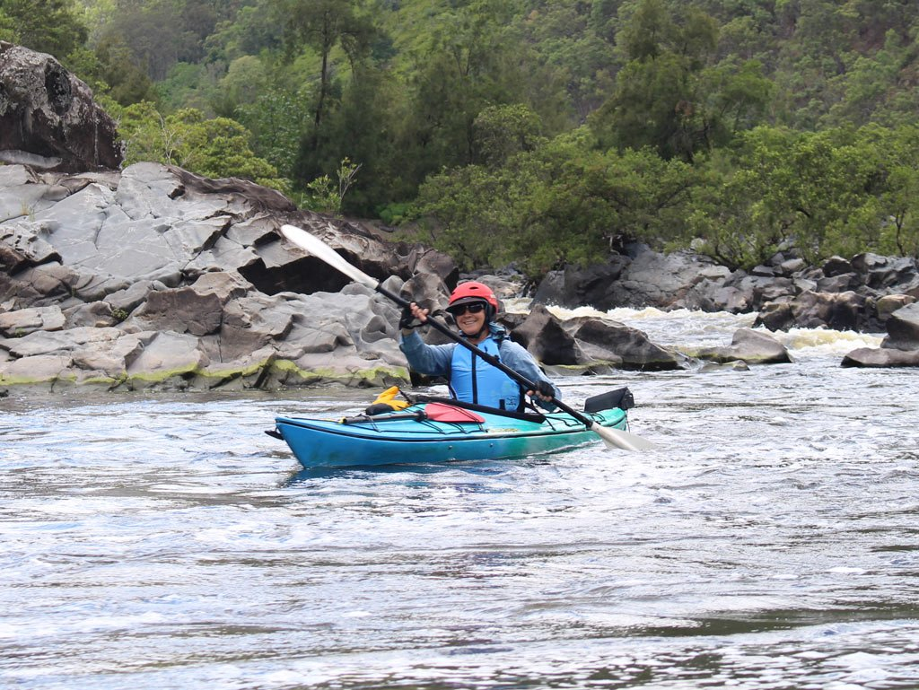Smiling kayaker in white water rapid on Nymboida River