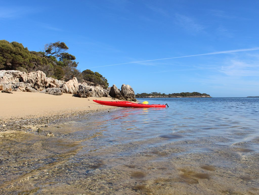 Red kayak on beach near shallow water at Coffin Bay in South Australia