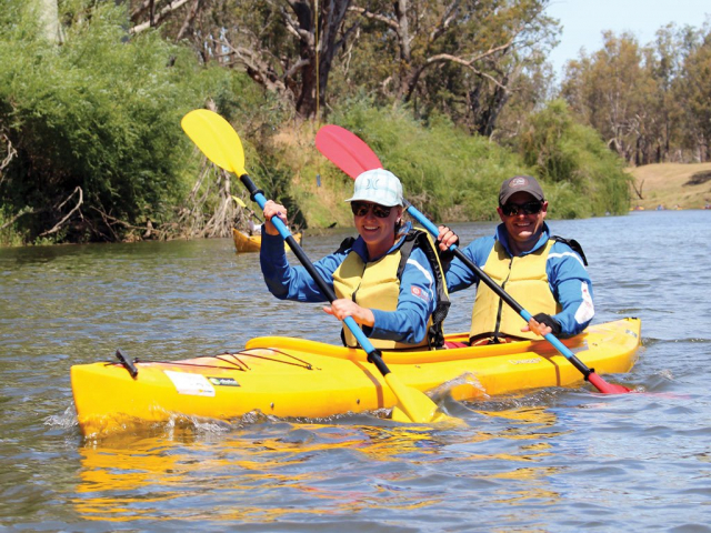 Two happy kayakers in a yellow double kayak on the Macquarie River in Wellington